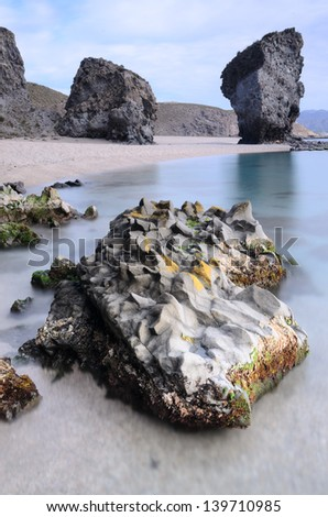 Long exposure photograph of a volcanic rock and christal waters in the beach known like La Playa de Los Muertos ( Beach of the Dead ). Belongs to the national park of Cabo de Gata. Carboneras, Spain - stock photo