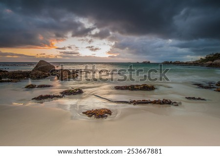 Long exposure photography of waves crashing over rocks at sunrise with storm clouds building - stock photo
