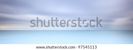 Long exposure photography panorama 3:1 with soft sea and cloudy sky. 2 minutes time exposure. - stock photo