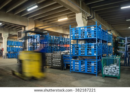 long exposure picture of an industrial hall, with big blue, green, and grey metallic bins, containing different elements which make up exhaust pipes and accessories, and a forklift passing by - stock photo