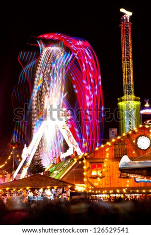 long exposure pictures of amusement park rides and wheels at night - stock photo