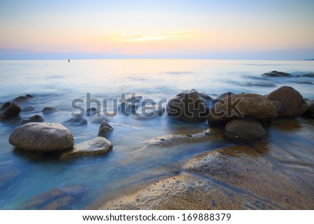 Long exposure scene of incoming waves over rocks on a Rayong beach in sunset time, Thailand