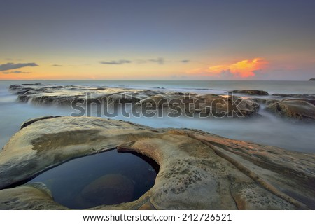 Long Exposure Seascape with stones at the beach during beautiful sunset (soft focus, shallow DOF, slight motion blur)  - stock photo