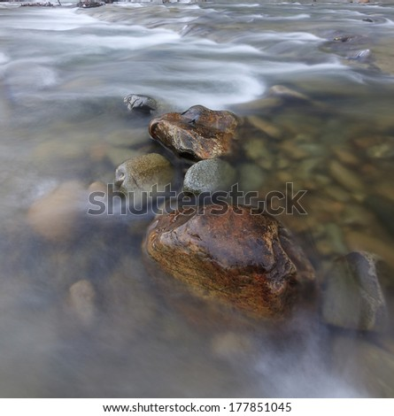 Long exposure shot of a river with rocks - stock photo