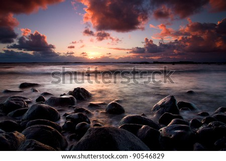 Long exposure shot of beautiful sunrise in Maui, Hawaii. Black lava stones in foreground against a quiet ocean and sun in background - stock photo