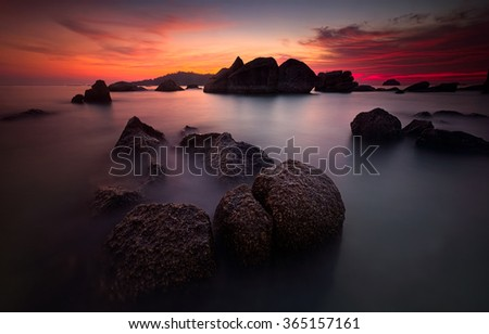 Long exposure shot of sunset scenery during high tide with unique rocks formation in Pangkor island, Malaysia. Focus on rocks in the foreground, visible noise due to long exposure. - stock photo