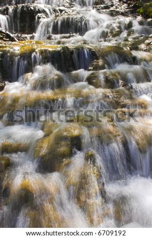 Long exposure shot of the water running through the waterfall - stock photo