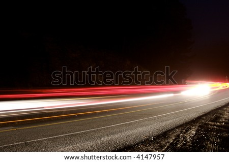 Long exposure showing the blur of passing cars on mountain road on a foggy night