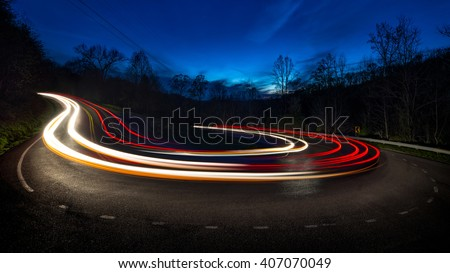 Long exposure showing the movement of traffic around horseshoe curve in the Appalachian mountains - stock photo