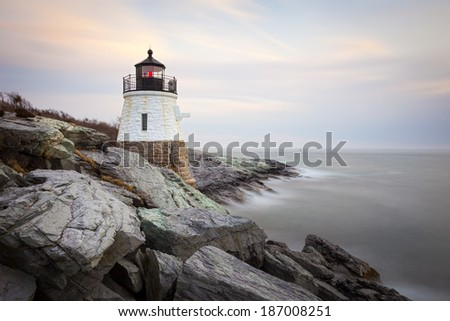 Long exposure sunset picture of Castle Hill Lighthouse at night in Newport, Rhode Island, USA on a rocky coastline of the Atlantic ocean. / Castle Hill Lighthouse at Sunset