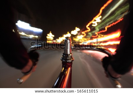 Long exposure taken from a camera fixed  on a fixed gear bicycle at night. In the forehand a close up of the handlebar. - stock photo