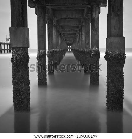 long exposure under the pylons, black and white image - stock photo