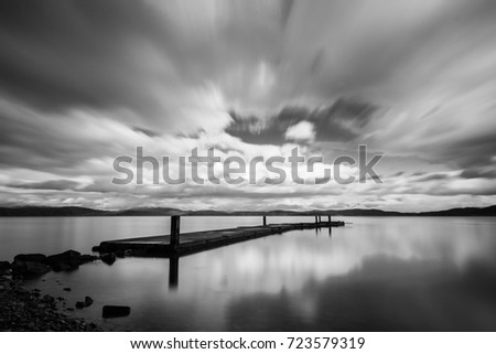 Long exposure view of a pier on a lake, with moving clouds and perfectly still water