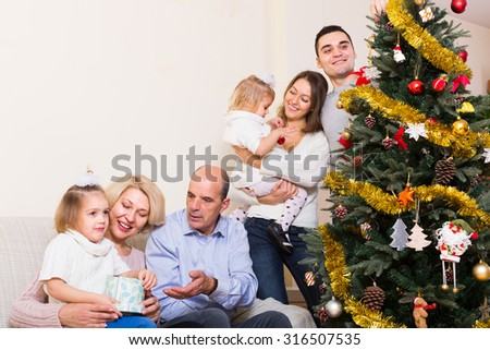 Long family with grand children decorating New Year tree - stock photo