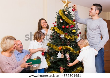 Long family with grand children decorating New Year tree at apartment - stock photo