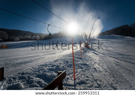Long fast ski slope with working snow cannons at sunny day