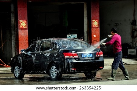 Long Feng, China - March 5, 2013:  Worker at a local car wash shop hoses suds off a customer's automobile using a high-powered hose - stock photo