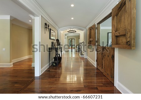 Long foyer with wooden barn doors into living room - stock photo