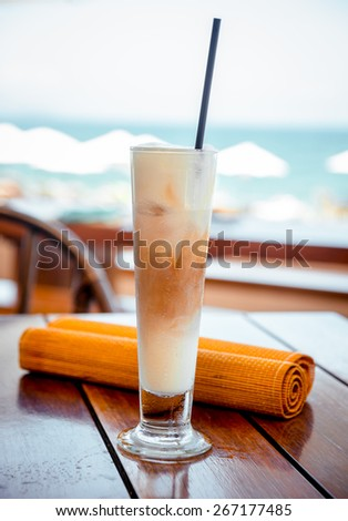 Long glass of coffee and milk on the table. On the beach background. Restaurant - stock photo