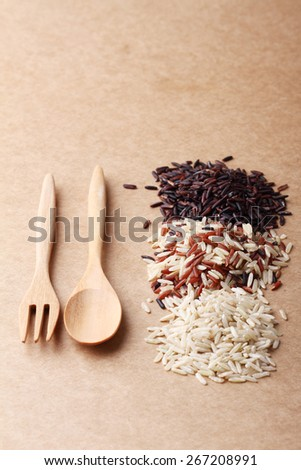 long grain rice,brown rice, with wooden spoon and fork on brown background - stock photo