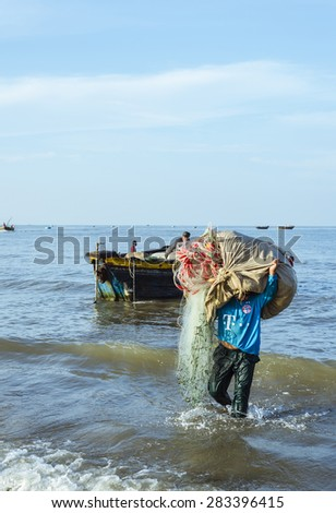 Long Hai, Ba Ria - Vung Tau, Vietnam - 31 May 2015: A fisherman carrying net back home from a long trip at Long Hai, Ba Ria - Vung Tau, Vietnam