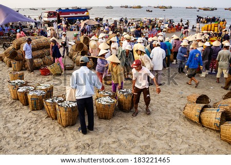 LONG HAI BEACH, VIETNAM - MARCH 15, 2008. A traditional fish market on the beach in Long Hai, Vung Tau, Vietnam. This market only happens in early morning. - stock photo