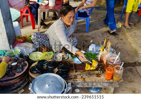 LONG HAI, VUNG TAU, VIETNAM - DEC 21, 2014. Vietnamese fast food (Banh Xeo and Banh Khot) vendors at Long Hai fish market on early morning. The local market only happens in early morning. - stock photo