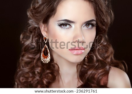 Long hair. Beautiful brunette girl model with fashion earrings. Makeup, luxury jewelry, wavy hairstyle. Woman isolated over dark studio background. - stock photo