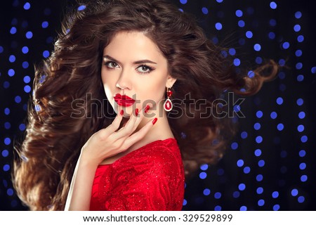 Long  hair. Beautiful brunette. Makeup. Luxury fashion style, manicure, cosmetics. Attractive young woman model posing on holiday blue lights background.