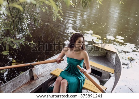 long hair brunette in a dress sitting on the boat