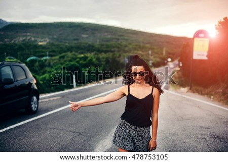 Long hair brunette tourist girl walking on the road