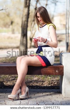Long hair girl sitting on bench with mobile phone at spring park. - stock photo