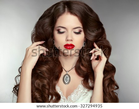 Long hair. Makeup. Beautiful woman with wavy hairstyle and evening make-up.  Jewelry. Beauty fashion girl portrait. Elegant lady with diamond pendant. - stock photo