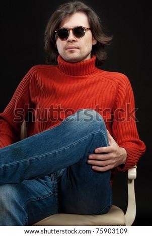 Long hair man wearing sunglasses sitting in armchair - stock photo