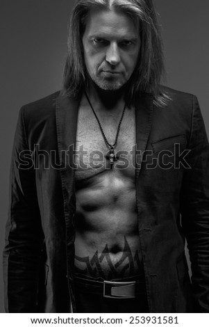 Long hair middle age male with naked torso and a suit possing on gray background. - stock photo