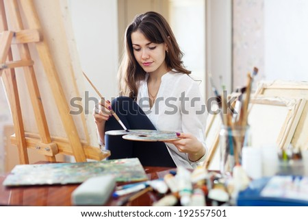 Long-haired beautiful artist paints on canvas in workshop - stock photo