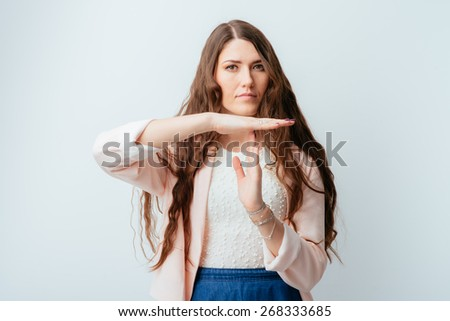 long-haired beautiful brunette girl shows timeout hands, isolated on white background - stock photo