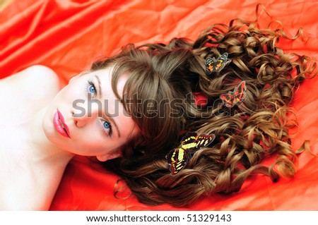 long haired beautiful girl with butterfly in her hair over the red - stock photo