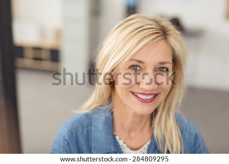Long-haired blond woman with a joyful facial expression smiling at camera with blue eyes and white teeth, portrait indoors - stock photo