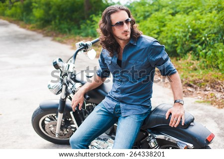 Long-haired brunette guy in sunglasses jeans and a denim shirt posing on a black custom motorcycle - stock photo