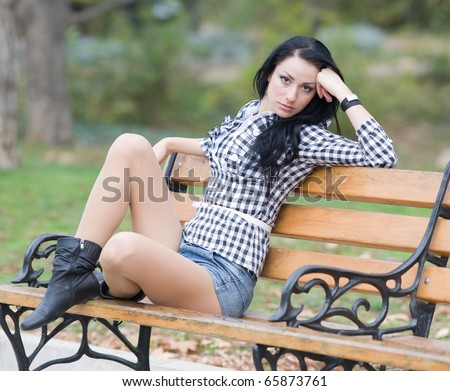 Long-haired brunette in shorts on bench in park