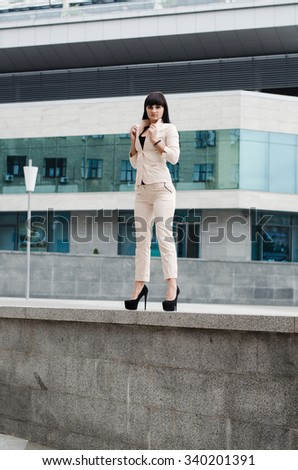 Long-haired brunette on high heels and urban background