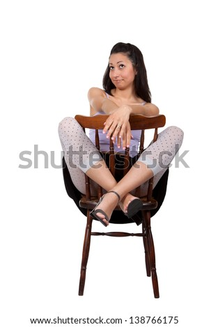 Long-haired brunette woman is sitting on a chair, make grimaces, isolated on white background
