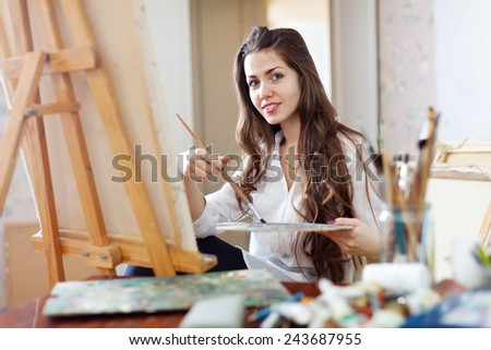 Long-haired female artist paints picture on canvas with oil paints in her workshop - stock photo