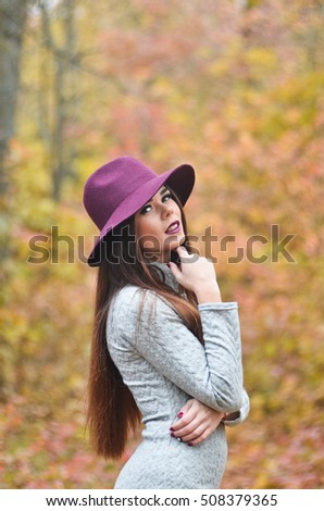 Long-haired girl in a burgundy hat in the middle of autumn forest.