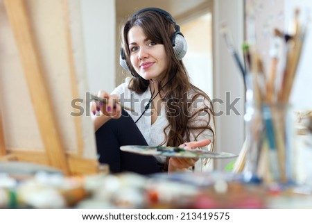 Long-haired girl in headphones  paints with oil colors and brushes on canvas in workshop interior - stock photo