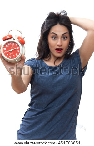 long-haired girl looks shocked at the alarm clock, business woman isolated on a gray background. - stock photo