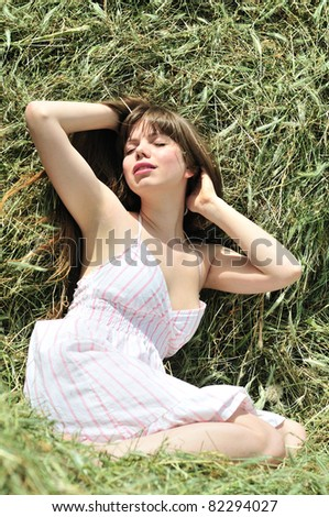 long-haired girl relaxing in the dry grass - stock photo