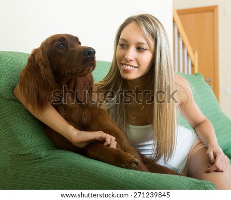 Long-haired girl sitting on sofa at home with red Irish setter  - stock photo