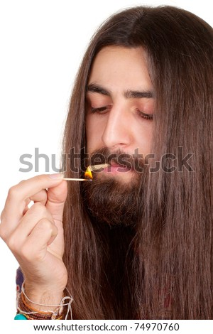 Long-haired hippie man smoking cigarette or marijuana joint